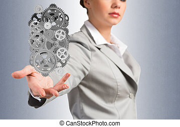 business woman holds up a mechanism of gears