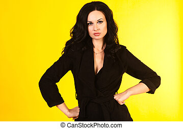 Business woman in a black suit, isolated on yellow background
