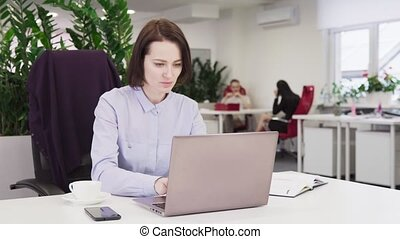 Business woman in a blue shirt working on a laptop in office