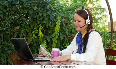 business woman in a cafe talking through a headset