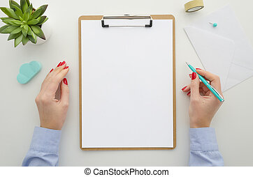 Business woman in blue shirt holds pen. clipboard mock up with A4 size white card, isolated on white desk. Top view flat lay. Template paperwork, financial reports,resume, brief, form, contract.
