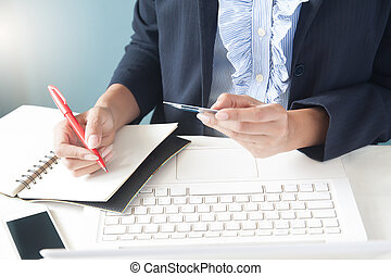 Business woman in dark suit holding credit card, using laptop and writting on notebook, Business and online shopping concept