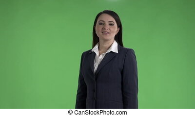 Business woman in dark suit talking to camera against a green screen medium shot