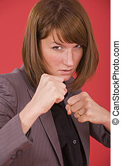 business woman in fighting stance on red background