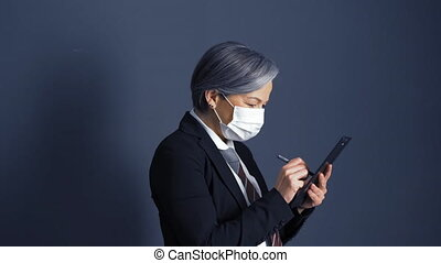 Business woman in protective mask with gray hair signs a ...