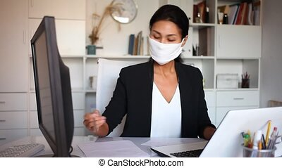 Business woman in protective medical mask using laptop at ...
