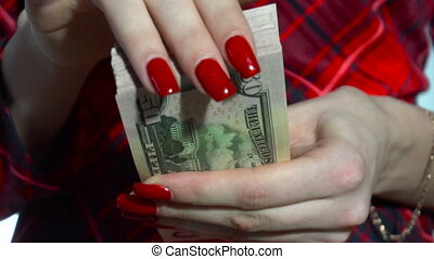 business woman in red dress counts a pack of money in hands in slow motion