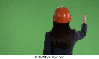 Business woman in safety helmet showing something behind her against green screen
