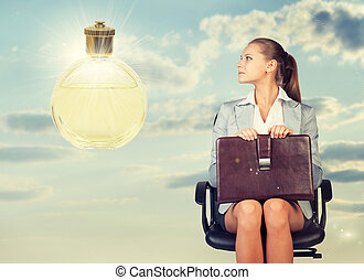 Business woman in skirt, blouse and jacket, sitting on chair, holding briefcase imagines perfume. Against background of sky, clouds