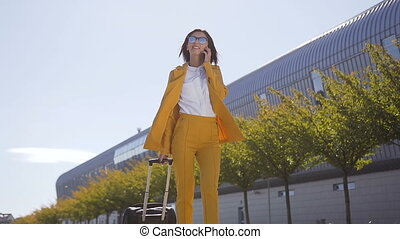 Business woman in suit and sunglasses talking on the smartphone while walking with hand luggage near train station or airport . Young woman happy using mobile phone app for conversation