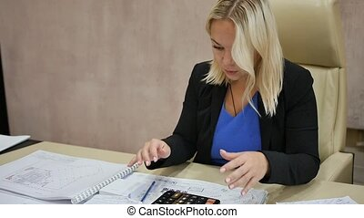 Business woman in the office. Close up upset blonde is thinking about mistakes at work. Portrait of a sad, wrinkled girl working in the office