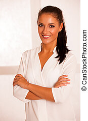 Business woman in the office gesturing confidence with arms crossed
