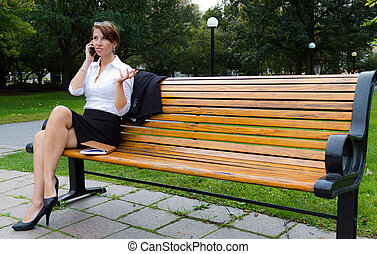 Business woman in the park talks on mobile phone