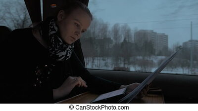Business woman in train working with pad and papers