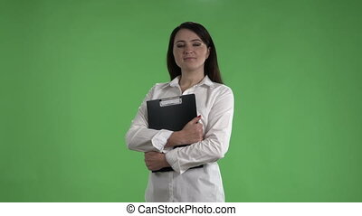 Business woman in white shirt with folder for papers against a green screen