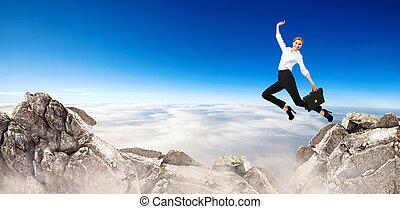 Business woman jumps through the gap between hills.