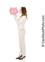 Business woman kissing a piggybank.