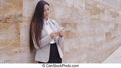 Business woman leaning against wall texting - Satisfied...