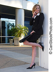 Business woman leaning on pillar