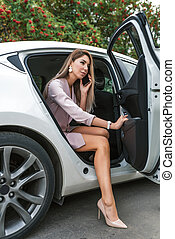 business woman leaves car, taxi rental, car sharing, calling ordering business VIP taxi, calls on her smartphone, listens voice message. In summer city, business transport, communication smartphone.