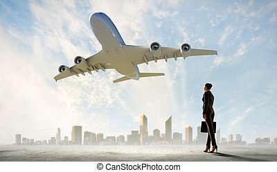 Business woman looking at airplane in sky - Image of...