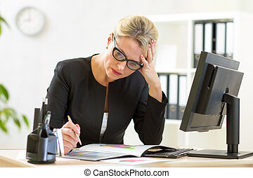 business woman looking at business papers in office