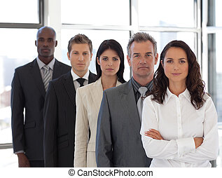 Business woman looking at camera with group in background
