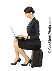 Business woman looking at notebook sitting on suitcase