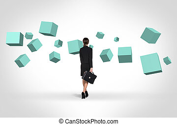 Business woman looking at turquoise cubes