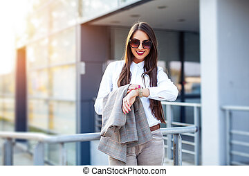 Business woman looking at watch at office building