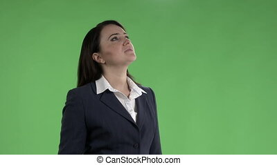 Business woman looking up and checking schedule on departure board against a green screen.