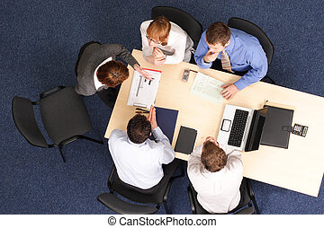 business woman making presentation to group of people. Aerial shot taken from directly above the table.