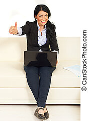 Business woman on couch gives thumbs
