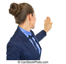 Business woman pointing on copy space. rear view