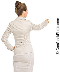 Business woman pointing on copy space . rear view