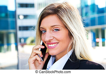 Business woman portrait outdoors talking at the phone