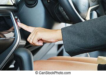 Business woman push an engine start button, close up.