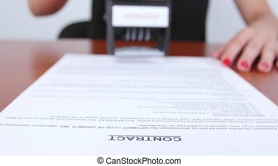 Business-woman puts a rectangular stamp of the company on the document. Close up