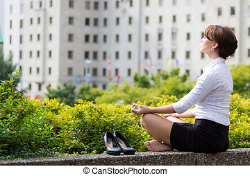 Business woman relaxing with yoga in the city