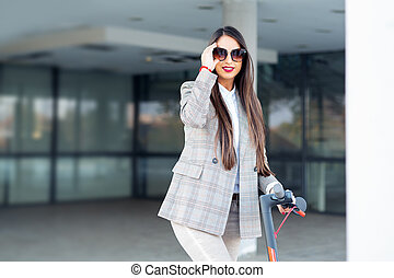 Business woman riding a scooter in the street