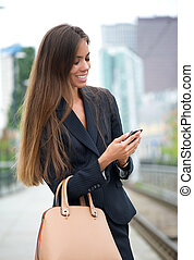 Business woman sending message on phone