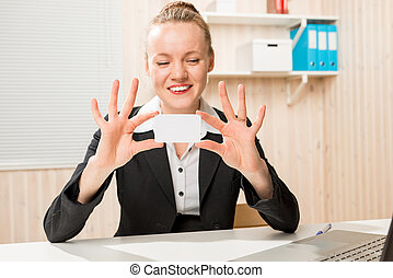 Business woman showing a small card for an inscription in the office