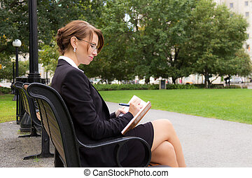 Business woman sits on parks bench and writes in her journal