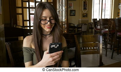 Business woman sitting at a table in restaurant and watching media content on her smart phone