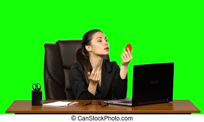 Business woman sitting at desk in leather chair and paints her lips looking in a red mirror. Green screen