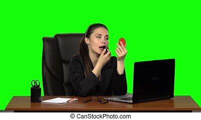 Business woman sitting at desk in leather chair and paints her lips looking in a red mirror. Green screen. Slow motion