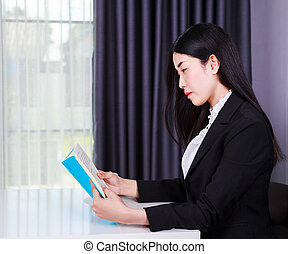 business woman sitting at the desk and reading a book