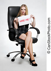"Business woman sitting on a chair holding a card board with the text message ""Hire me"" and beging for a job."