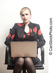 Business woman sitting on chair with notebook in office