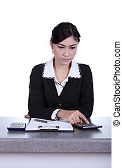 business woman sitting on her desk and using the calculator